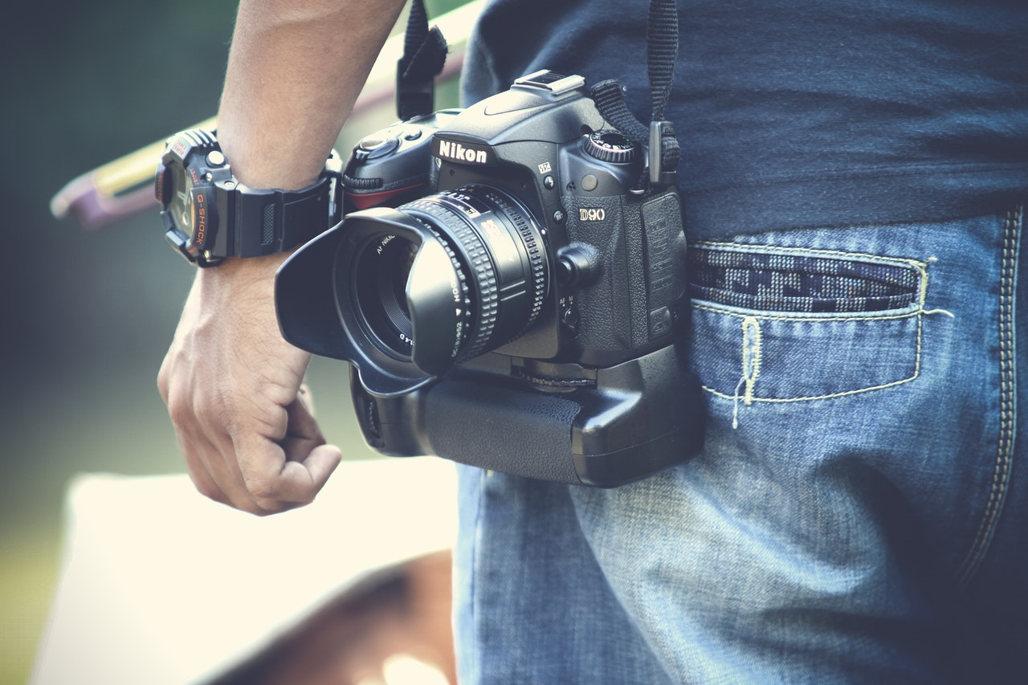 man with camera strap around shoulder