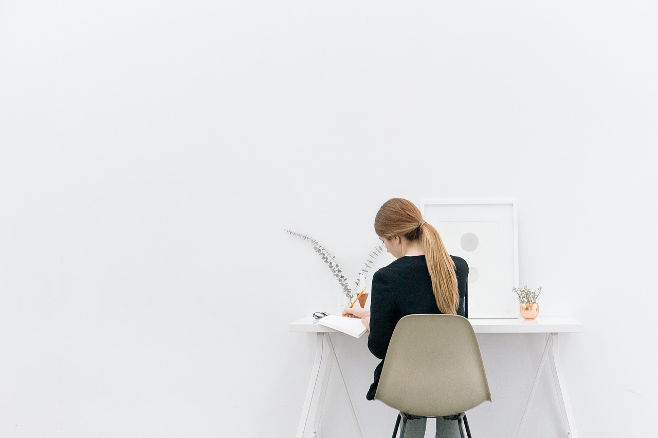 woman sitting at desk writing